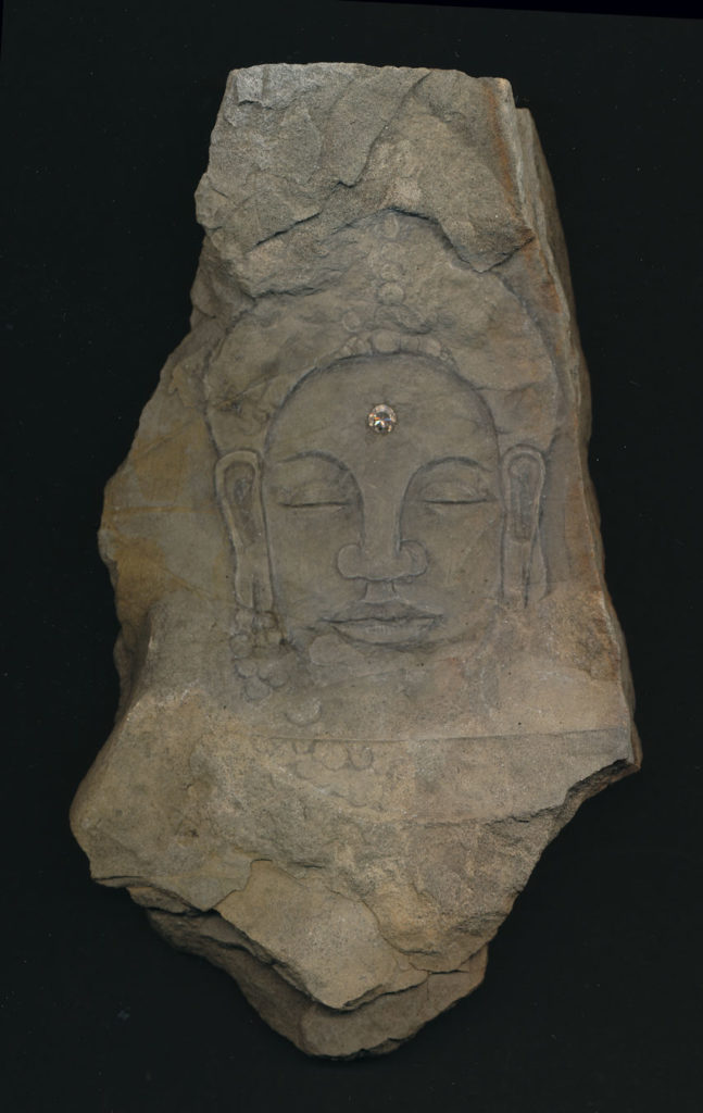 an image of the buddah etched into a stone and appearing to come out of the stone.